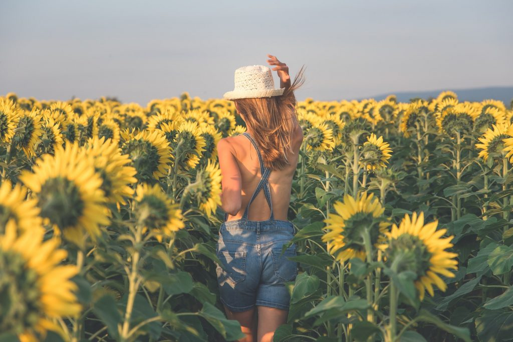 Summer day and happy young woman in the sunflower field.